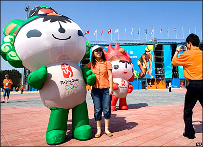 A tourist poses with the 2008 Beijing Olympics mascot Fuwa outside the Chaoyang Park Beach Volleyball stadium in Beijing.