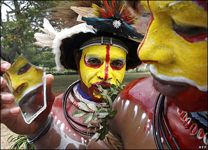 Tari wigmen from Papua New Guinea check their face paint 