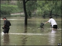 North Korean passers-by make their way through a flooded street in Pyongyang, North Korea