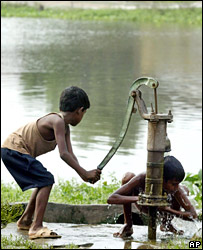 A boy pumps water for another to bathe at a village in Samastipur district, in Bihar state (11 August 2007)