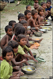 Children eat food at a relief camp in a village in Begusarai district, Bihar state (14 August 2007)