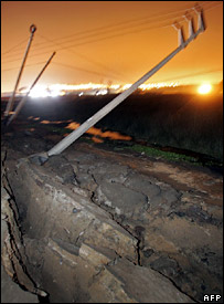 A crumpled road and fallen power lines in Lima