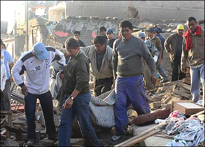 Residents remove the body of a quake victim in Pisco
