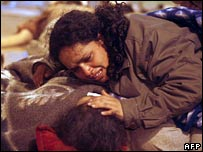 A mother comforts her injured son in Pisco