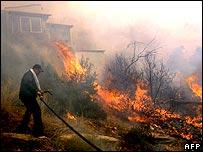 Мужчина, пытающийся погасить пожар у дома