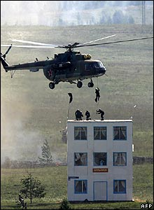 Men dropping from helicopter onto roof