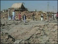 Villagers survey the destruction caused by the bombings