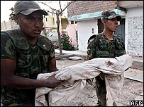 Soldiers carry the corpse of a child in Pisco, Peru