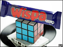 Wispa bar, on top of a Rubik's cube and cassettes