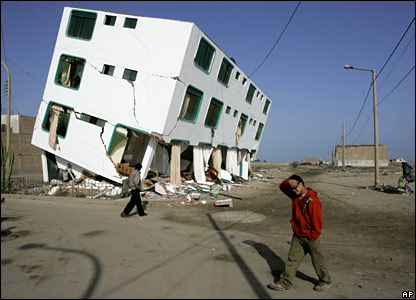 Residents walk pass a building that failed during the earthquake that shook Pisco, Peru.