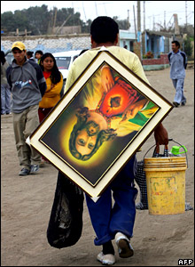 Earthquake refugee with a religious picture in Peru