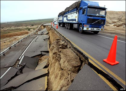 A truck drives along a highway ripped open by the Peru earthquake.