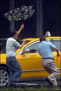 Wind-blown men dash to taxi in Hsintien, Taipei County, on 18 August