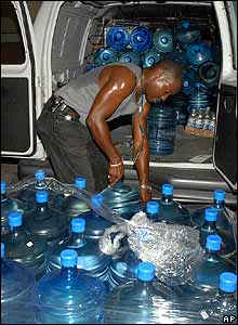 Man loads bottled water into his van in Kingston, Jamaica, on 17 August