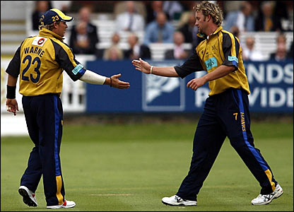 Shane Warne (left) is congratulated by bowler Sean Ervine after the two combined to dismiss Kyle Coetzer