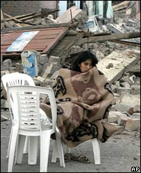 Woman sleeping outside wrecked house in Pisco