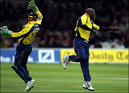 Phil Mustard (left) and Otis Gibson celebrate taking the wicket of Sean Ervine