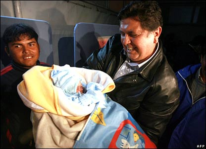 President Alan Garcia holds Rafael Jesus, a baby born after the earthquake at an improvised hospital in Pisco