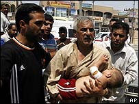 Man rushes injured baby to hospital in Sadr City after the mortar attack on 19 August
