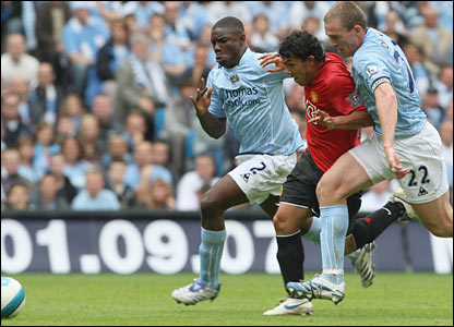 Richard Dunne and Micah Richards challenge Carlos Tevez