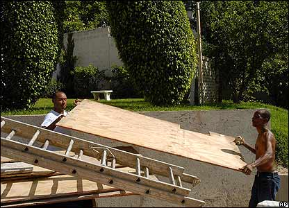 A father and son handle plywood for boarding up their house in Kingston, Jamaica, on 18 August