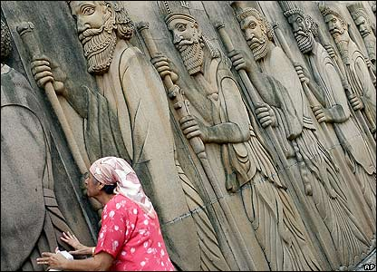 An Indian Parsi woman touches statues on the walls of a Fire Temple in Mumbai