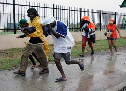 Jamaicans run toward a shelter in the capital Kingston