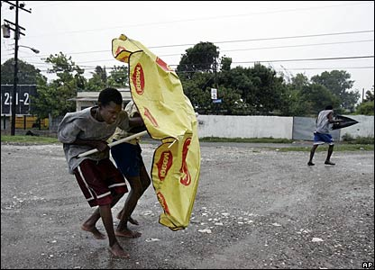 One Jamaican tries using an umbrella to resist the winds