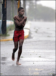 A young boy runs under the rain and wind in the capita