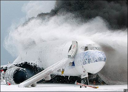 Burning plane is sprayed with extinguisher foam at Naha airport - 20/08/07 (Picture credit: AP Photo/Kyodo News, Hiroshi Tsujimoto)