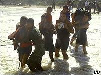 Grupo de personas atraviesan un río durante una evacuación