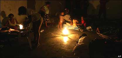 Varias personas en un refugio, a la luz de una fogata