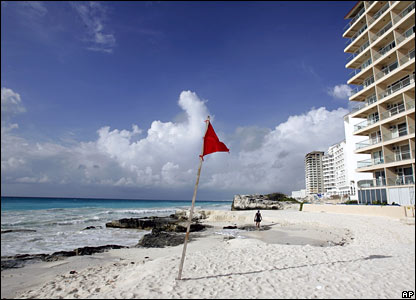A man walks along the beach in Cancun,  which has seen an exodus of  thousands of tourists who are attempting to leave before Hurricane Dean arrives.