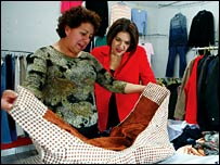 Alicia Hernandez (L) showing clothes she sells to Mary Ellen Iskenderian (R)