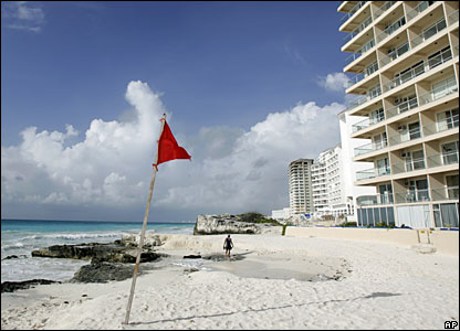 1 A man walks along the beach in Cancun next to a red flag warning of the arrival of Hurricane Dean in Cancun, Mexico