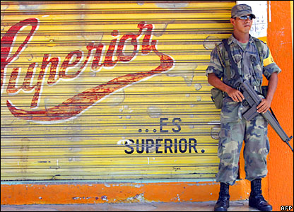 A Mexican Army soldier stands guard near a shop in Chetumal, Mexico