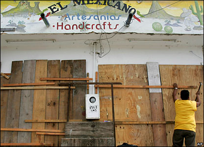 Israel Martinez boards up the windows of his shop in Tulum, Mexico,