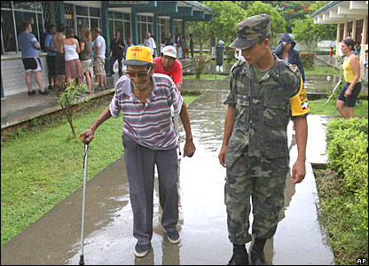 An army soldier helps an elderly man at a storm shelter before Hurricane Dean arrives in Chetumal