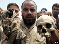 An Iraqi man holds a human skull from a mass grave containing 30 bodies in Basra. Police said the grave contained victims of the suppression of the 1991 uprising. (19 August 2007)