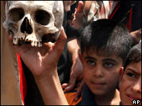 Iraqi boys hold a skull found in a mass grave near Basra