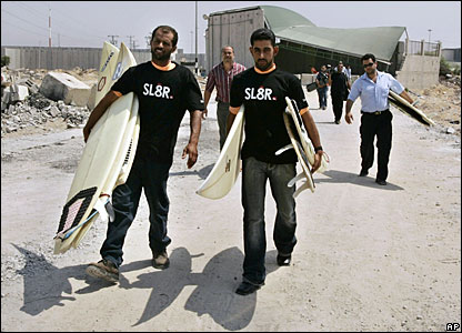 Palestinian men carry surf boards onto the beach