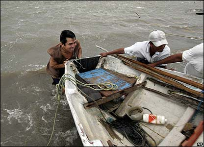 Fishermen work to remove a boat from the waters in Chetumal