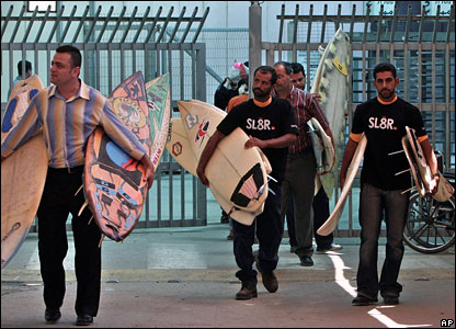 Palestinian men carry the donated surfboards.
