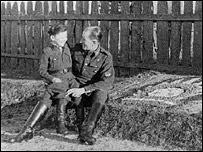 Una fotografía en blanco y negro muestra al joven Alex Kurzem sentado en la rodilla de un oficial