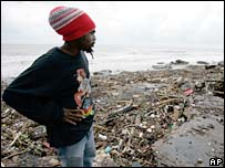 Jamaican man looks at an empty lot where his house once stood