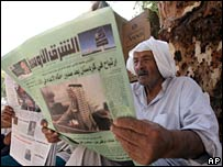 An Iraqi man reads a newspaper about the previous trial of Ali Hassan al-Majid