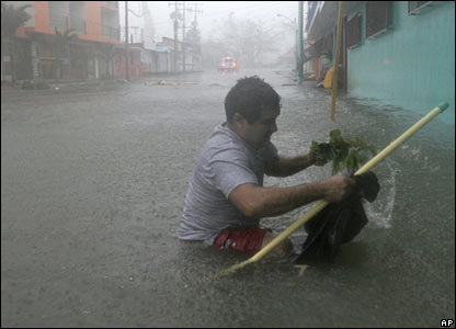 A man tries to make his way through a flooded street in Chetumal