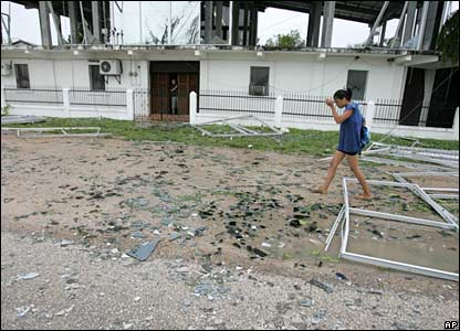 A woman walks through the debris from a damaged house in Corozal, north of Belize City