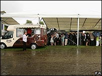 An ice cream van struggles to entice customers during a rain storm at Royal Ascot