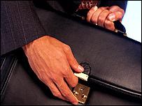 Un hombre cerrando un malet�n / Foto de archivo